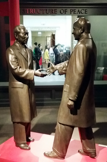 Life-size bronze figures of Zhou Enlai and President Nixon shake hands at the center of the Nixon Library in California.